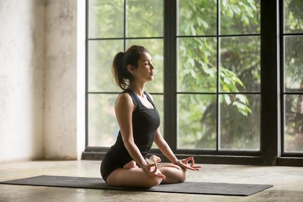 Jovem mulher atraente em padmasana pose, fundo de estúdio Foto gratuita