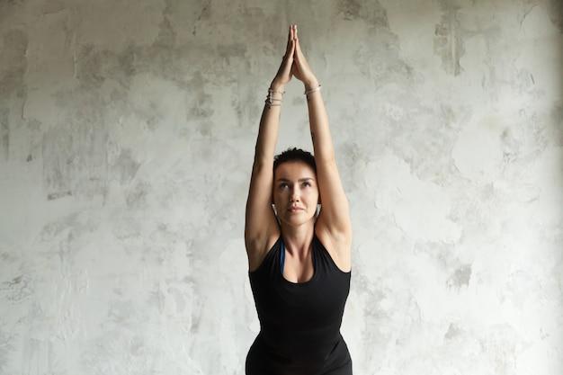 Jovem mulher atraente em pose de cadeira, fundo de parede vazia Foto gratuita