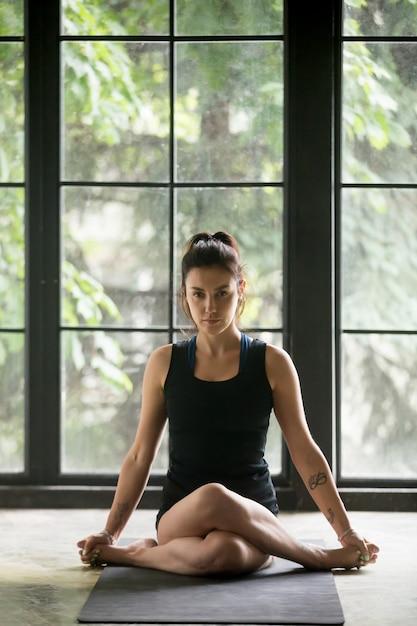 Jovem mulher atraente em pose de gomukasana, fundo de estúdio Foto gratuita