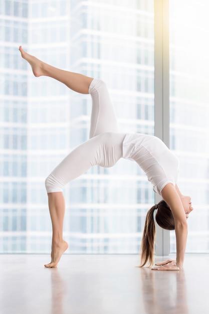 Jovem mulher atraente em pose de ponte contra a janela do piso Foto gratuita