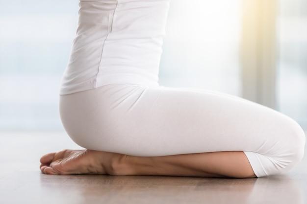Jovem mulher atraente em pose de vajrasana, closeup de pernas Foto gratuita