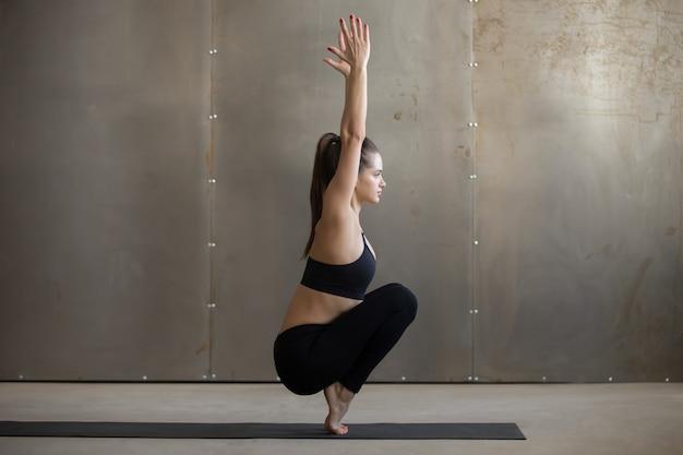Jovem mulher atraente em utkatasana pose, backgroun studio cinza Foto gratuita