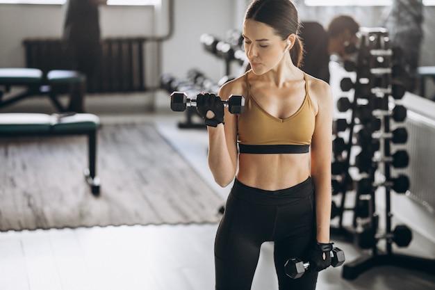Jovem mulher atraente, exercitar-se com halteres na academia Foto gratuita