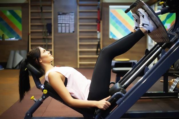 Jovem mulher atraente fazendo exercícios no ginásio de fitness. Foto Premium