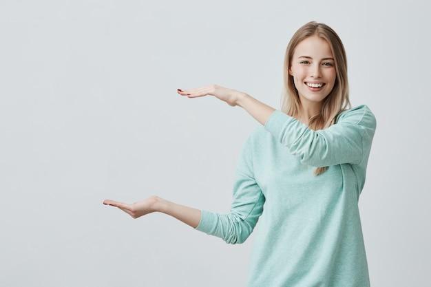 Jovem mulher atraente feliz na camisola azul clara, mostrando algo grande com as mãos Foto gratuita