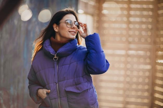Jovem mulher atraente no casaco de inverno azul Foto gratuita