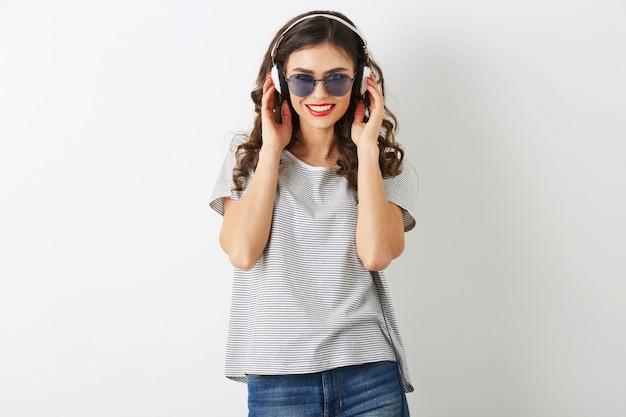 Jovem mulher atraente ouvindo música em fones de ouvido, usando óculos escuros, isolado no fundo branco, Foto gratuita