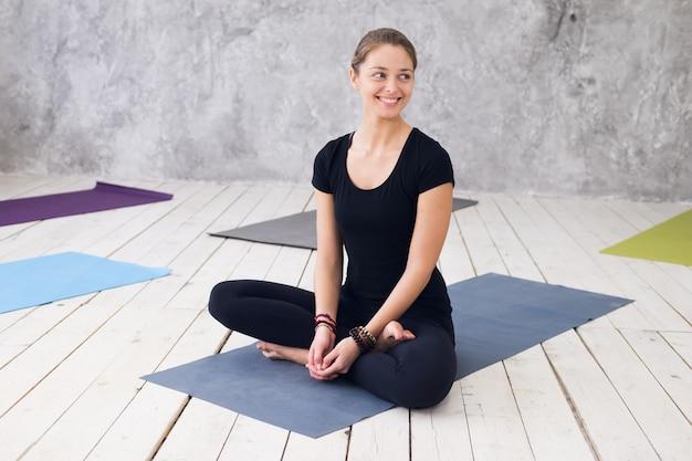 Jovem mulher atraente praticando ioga, sentado no exercício de ardha padmasana, meia pose de lótus. Foto Premium