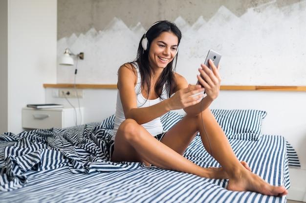 Jovem mulher atraente sentada na cama de pijama, sorrindo no quarto, emoção feliz, acordar de manhã, rindo, sexy, magra, ouvindo música em fones de ouvido, usando smartphone, tirando foto de selfie Foto gratuita