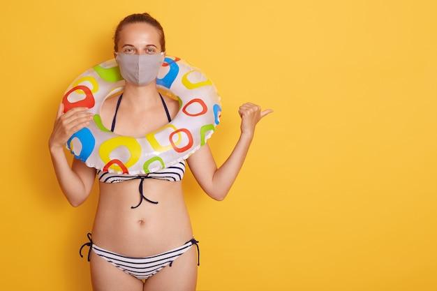 Jovem mulher atrativa no roupa de banho com anel de borracha na máscara médica isolada sobre a parede amarela, apontando de lado com o polegar, espaço da cópia para a propaganda. Foto gratuita