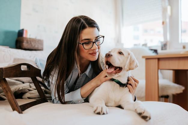 Jovem mulher atrativa que encontra-se no sofá com seus animal de estimação e descanso. Foto Premium