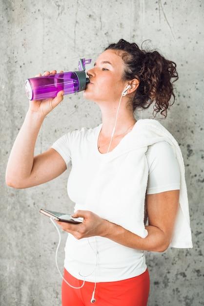 Jovem mulher bebendo água e ouvindo música no smartphone Foto gratuita