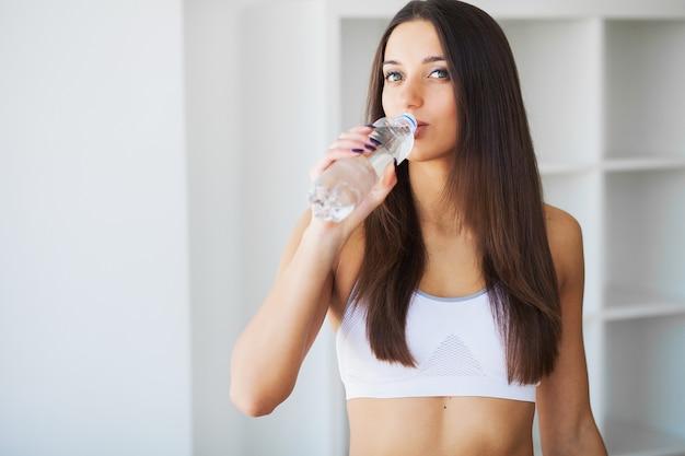Jovem mulher bebendo água. moça bonita que guarda a garrafa da água Foto Premium