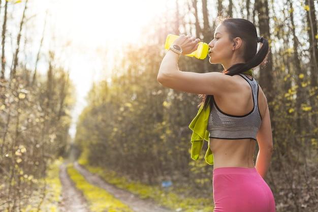 Jovem mulher bebendo água na natureza Foto gratuita