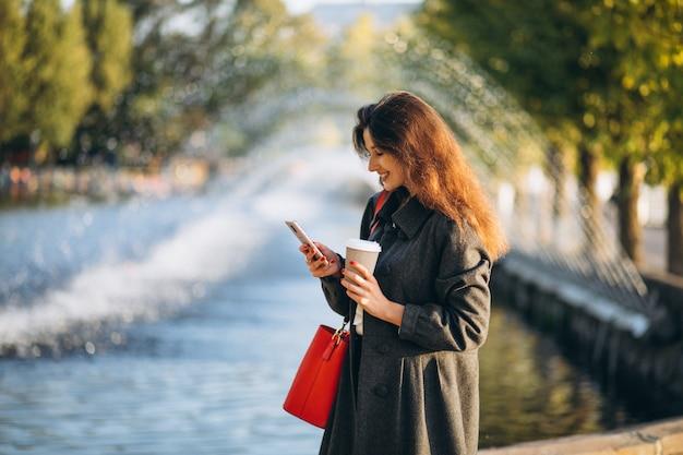 Jovem mulher bebendo café e usando o telefone no parque Foto gratuita