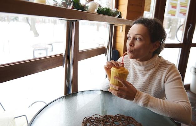 Jovem mulher bebendo em um canudo e olhando pela janela para uma natureza coberta de neve enquanto está sentada em um pequeno café de madeira Foto Premium