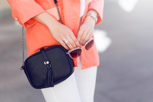 Jovem mulher bonita andando na cidade velha em roupas da moda casual glamour, jaqueta rosa. primavera ou outono, tempo ensolarado. detalhes. Foto gratuita