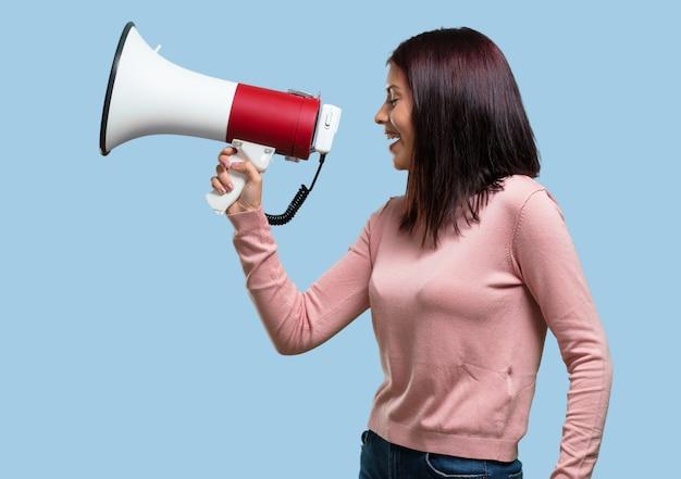 Jovem mulher bonita animada e eufórica, gritando com um megafone Foto Premium