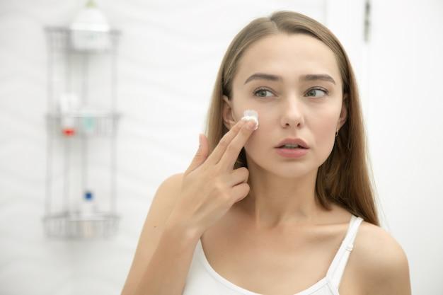 Jovem, mulher bonita, aplicando creme para enfrentar no banheiro Foto gratuita