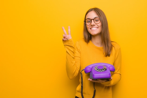 Jovem mulher bonita caucasiana mostrando o número dois. ela está segurando um telefone vintage. Foto Premium