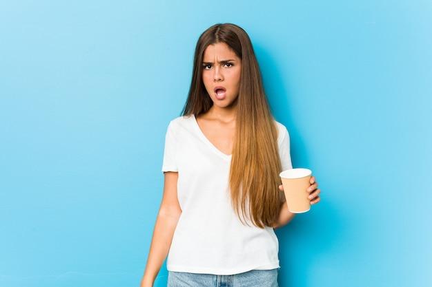 Jovem mulher bonita caucasiana segurando um café para viagem gritando muito irritado e agressivo. Foto Premium