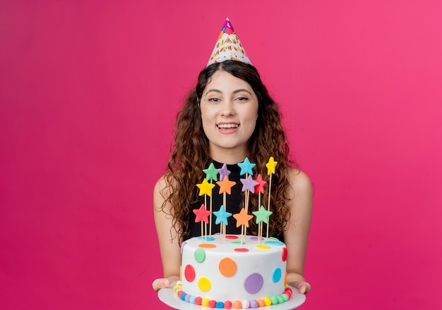 Jovem mulher bonita com cabelo encaracolado com um boné de férias segurando um bolo de aniversário hapy e conceito de festa alegre sobre rosa Foto gratuita