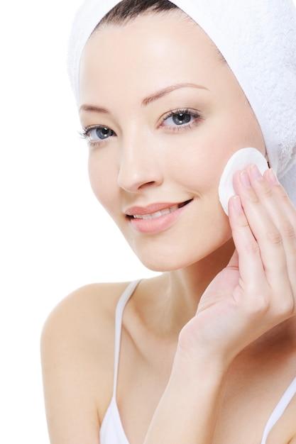 Jovem mulher bonita com cotonete limpando o rosto Foto gratuita