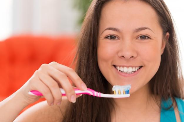 Jovem mulher bonita com escova de dentes Foto gratuita