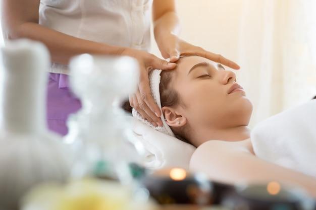 Jovem, mulher bonita, com massagem facial relaxante no spa. Foto gratuita