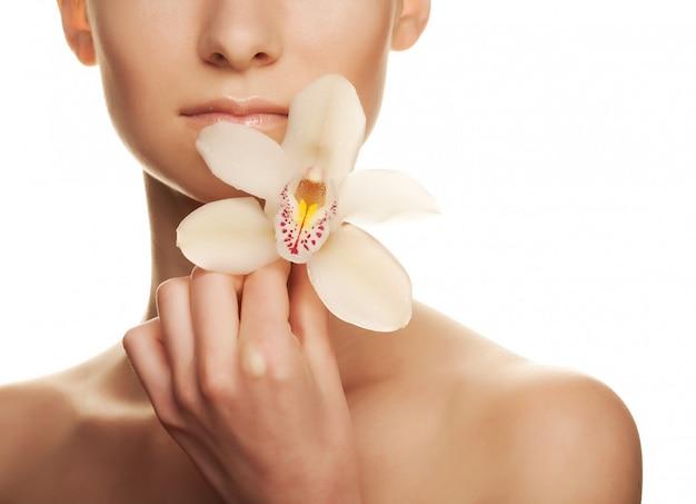 Jovem mulher bonita com orquídea branca Foto Premium