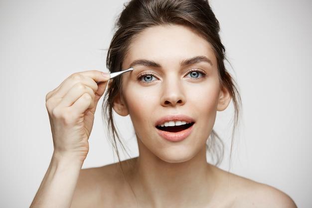 Jovem mulher bonita com perfeita pele limpa tweeze sobrancelhas. tratamento facial. Foto gratuita