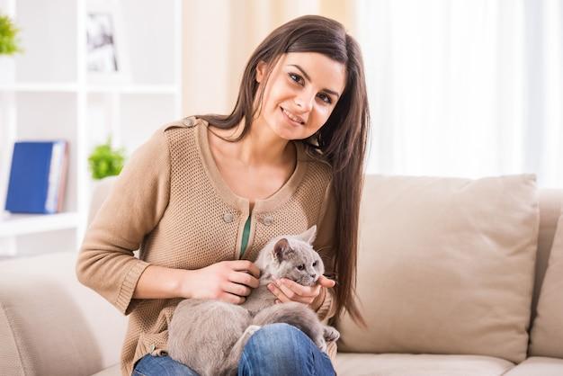 Jovem mulher bonita com seu gato no sofá em casa. Foto Premium