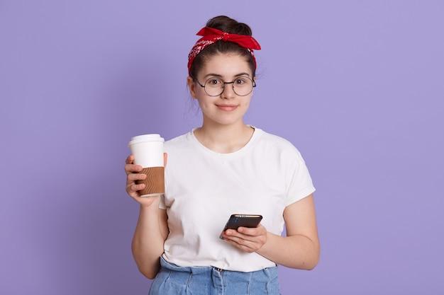Jovem mulher bonita com telefone inteligente e café para viagem, aluna sorridente posando isolada sobre o espaço lilás Foto gratuita