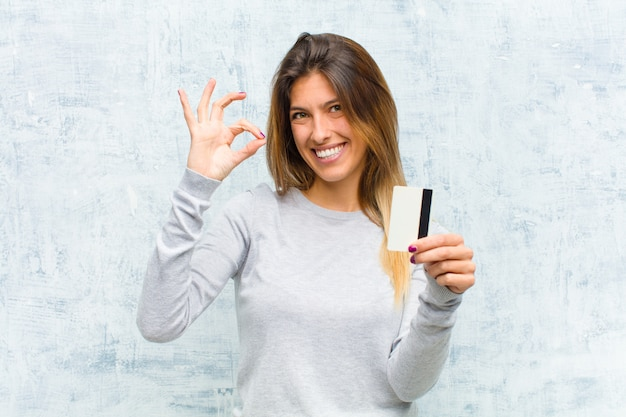 Jovem mulher bonita com um cartão de crédito contra a parede do grunge Foto Premium