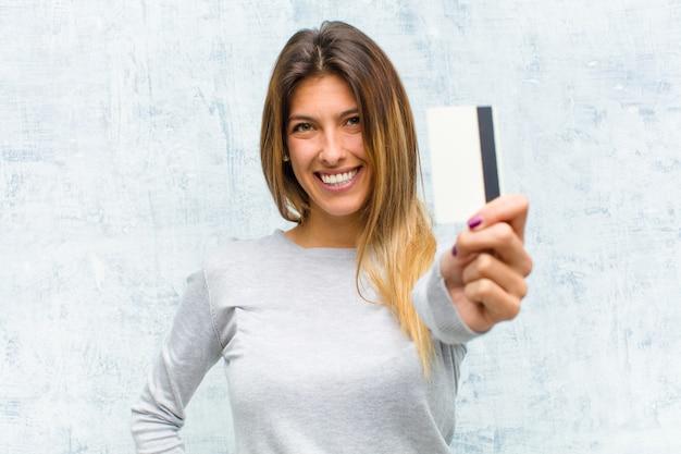Jovem mulher bonita com um cartão de crédito Foto Premium