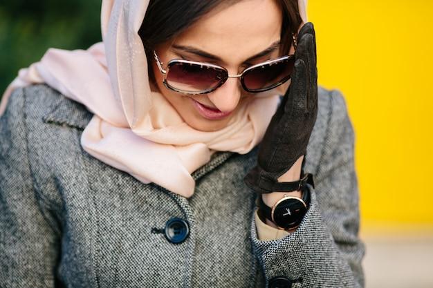 Jovem mulher bonita com um casaco sentada num banco do parque Foto gratuita