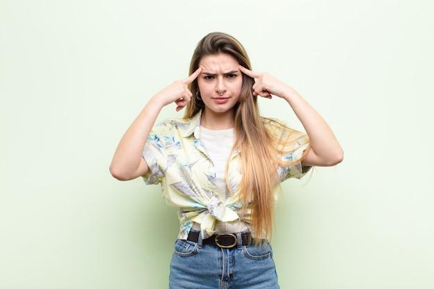 Jovem mulher bonita com um olhar sério e concentrado, de brainstorming e pensando em um problema desafiador Foto Premium