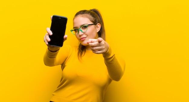 Jovem mulher bonita com um telefone inteligente contra fundo amarelo Foto Premium