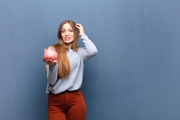 Jovem mulher bonita com uma parede azul de cofrinho com uma copyspace Foto Premium