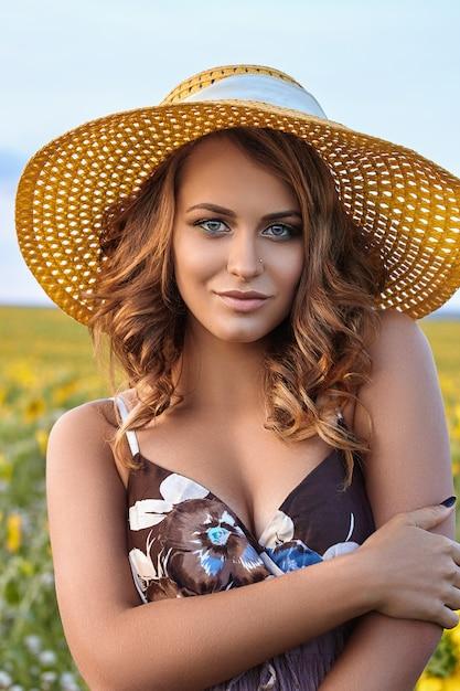 Jovem mulher bonita de chapéu em um campo de girassóis Foto Premium