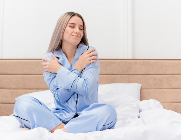 Jovem mulher bonita de pijama azul, sentada na cama, abraçando-se com os olhos fechados, sentindo emoções positivas no interior do quarto com luz de fundo Foto gratuita
