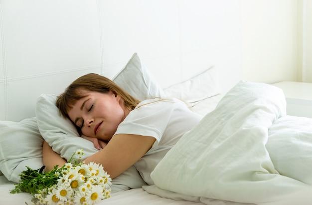 Jovem mulher bonita dormindo na cama com margaridas flores Foto Premium