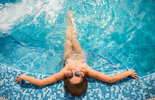 Jovem mulher bonita é relaxante na piscina. Foto Premium