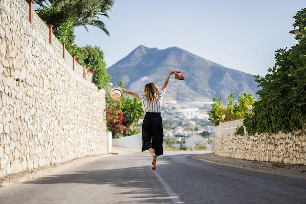 Jovem mulher bonita em férias pulando. em uma mão sandálias no chapéu de segunda mão. Foto gratuita