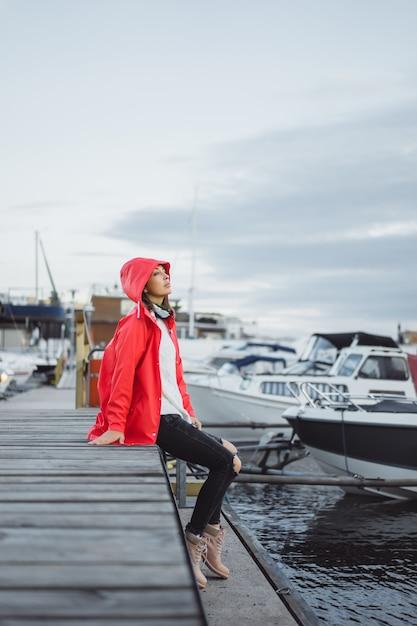 Jovem mulher bonita em um casaco vermelho no porto do iate. estocolmo, suécia Foto gratuita