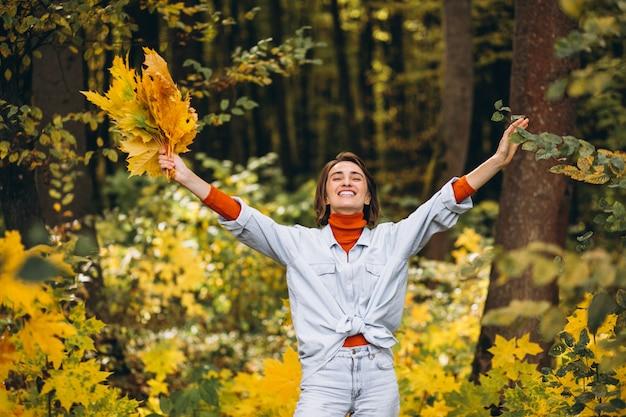 Jovem mulher bonita em um parque outono cheio de folhas Foto gratuita