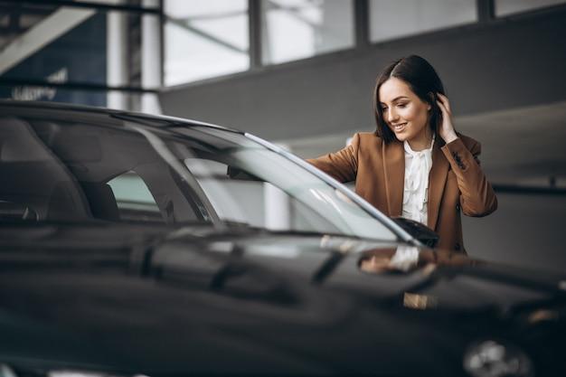 Jovem mulher bonita escolhendo o carro em uma sala de exposições Foto gratuita