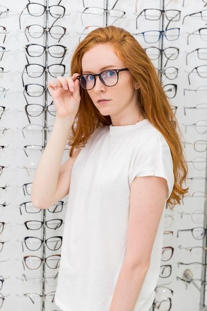 Jovem mulher bonita escolhendo óculos na loja de óptica Foto gratuita
