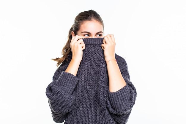 Jovem, mulher bonita, escondendo o rosto na camisola vermelha sonhadora olhando na câmera sobre parede branca Foto gratuita