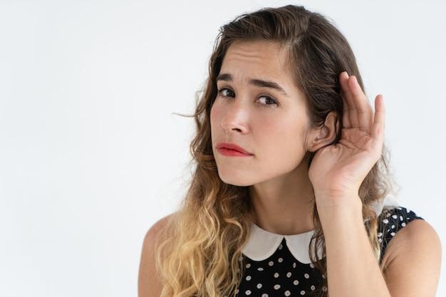 Jovem mulher bonita focalizada que guarda a mão perto da orelha e que olha a câmera. Foto gratuita